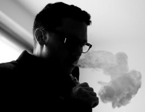 Man deciding which e-cigarette to use following news of surge in vapers in US