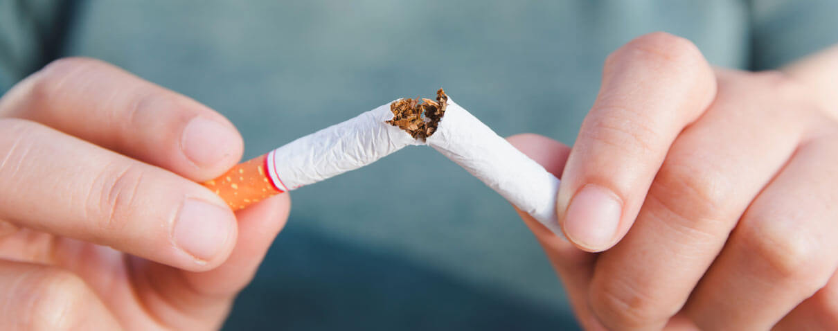 Man snapping cigarette in half