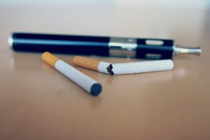 Two versions of e-cigarettes on a table with a snapped tobacco cigarette between them.
