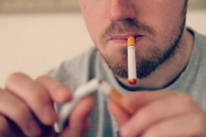 An E-Cigarette smoker snapping a tobacco cigarette as he quits the habit.