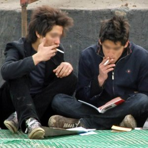 A pair of teenagers smoking cigarettes while reading info on the healthier alternative of e cigarettes from OK E - Cig