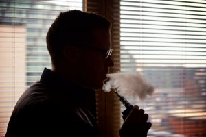 A Welsh man enjoys his e-cigarette, not knowing if his government will impose an e-cigarette ban.