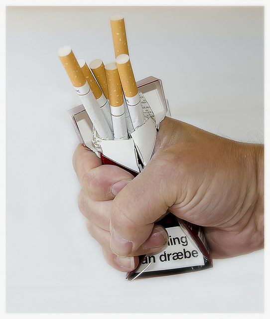 A person crushing his cigarettes before using an e-cig starter kit