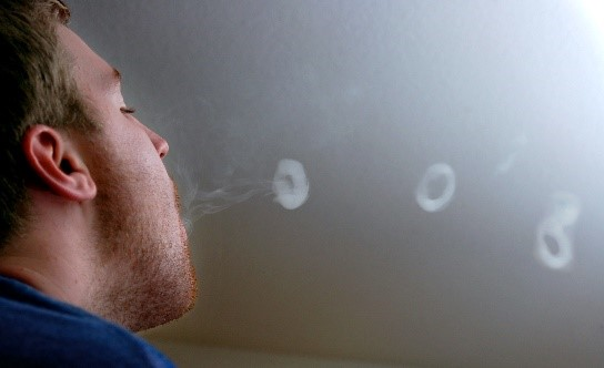A man blowing vape rings using an e cigarette
