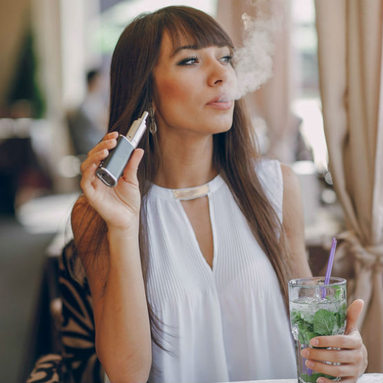 A lady enjoys using her e-cigarette at a bar. Are e cigarettes safe?