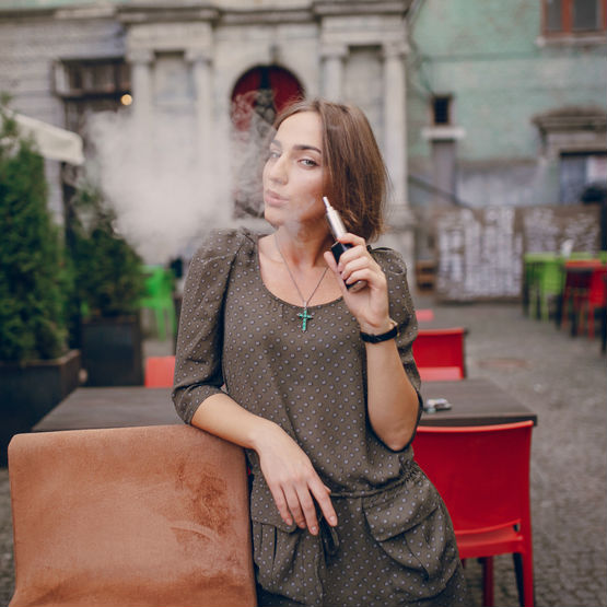 A lady uses her e-cigarette outdoors. Vaping in the UK.