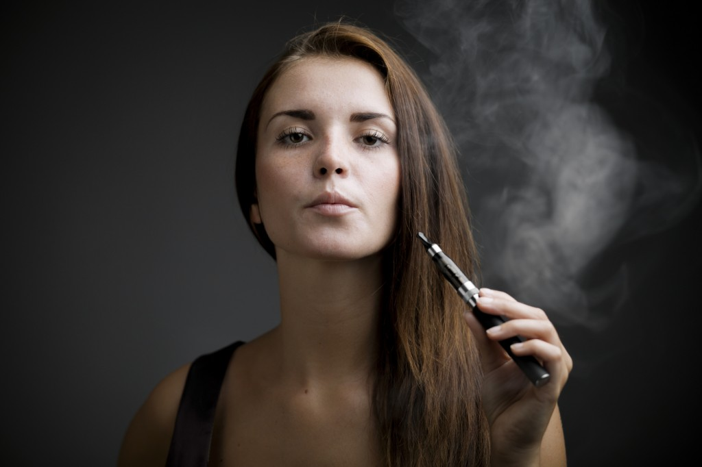 Elegant woman vaping with e-cigarette
