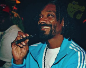 Rapper Snoop Dogg is pictured inhaling vape from his e-cigarette.