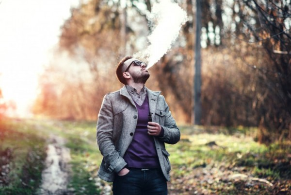 A fashionable man with beard uses his vape pen outdoors
