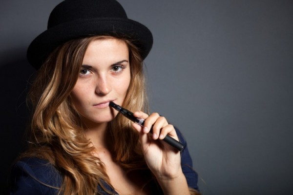 Elegant woman vaping, wearing a suit and hat