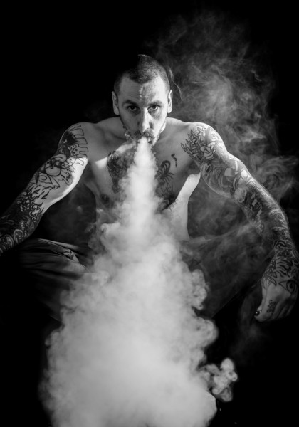 tattood man blowing smoke out of mouth isolated on black background.