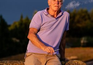 A handsome older man puffing on an e-cigarette